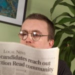 Male learner reading newspaper coverage of all-candidates meeting.