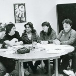 First women's group sitting at a table talking and learning