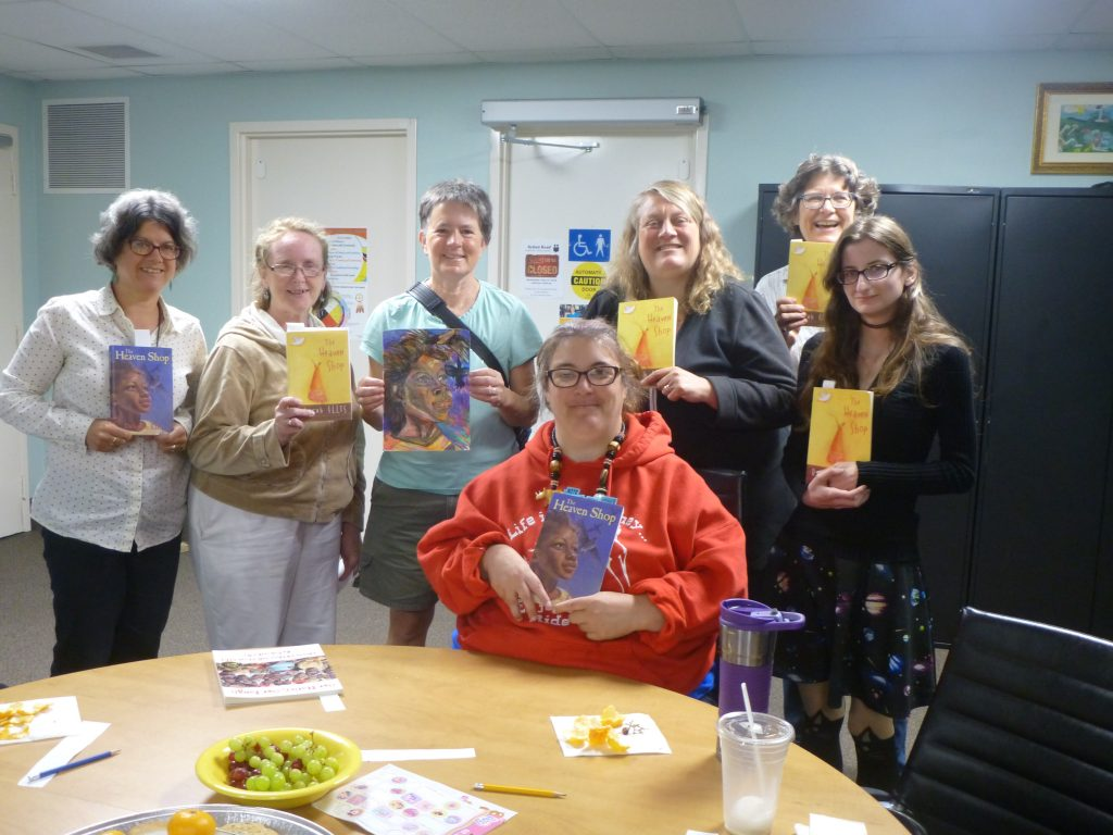 Happy learners and volunteers holding author Deb Ellis's book.