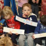 Kids holding signs with positive words related to learning.