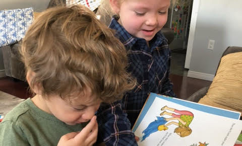 Young children looking at their new books gifted to them from Action Read.