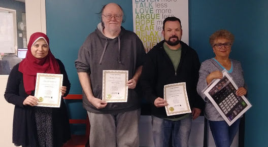 Four Action Read Cashier training participants holding their certificates of completion.