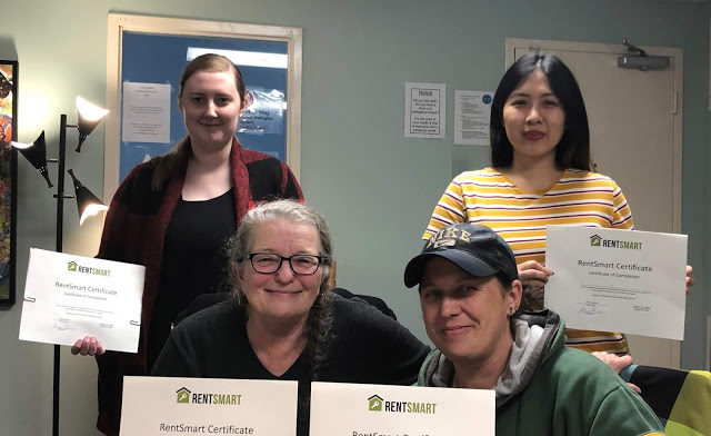 Four Action Read learners holding their RentSmart certificate of completion.